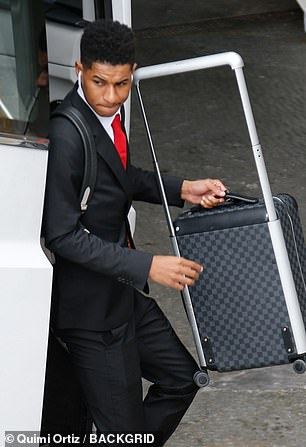 12301628-6924543-Marcus_Rashford_grabs_his_luggage_as_he_steps_off_the_team_coach-a-32_1555340332369